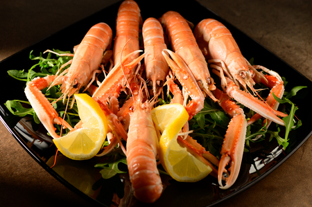 fresh grilled shrimps served on a plate with arugula or rocket and llemon Stock Photo