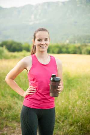 Beautiful young woman rests after a long run workout outdoor in nature Banco de Imagens