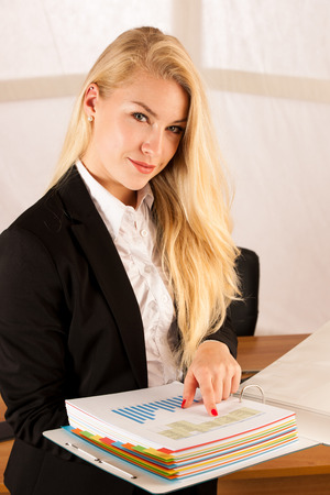 Beautiful young woman check data in a work folder in her office Imagens