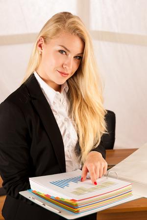 La bella giovane donna controlla i dati in una cartella di lavoro nel suo ufficio Archivio Fotografico