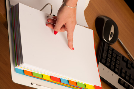 Woman hand on a front page of a business folder checking data Stock fotó