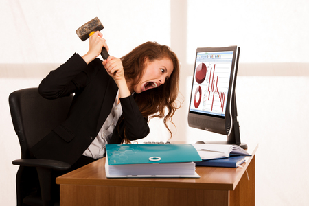 Angry business woman expressing rage at her desk in the office 스톡 콘텐츠