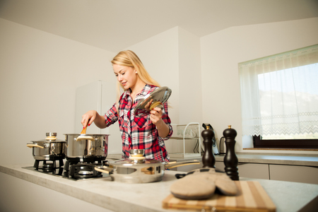 Beautiful young woman in kitchen cooks a delicious meal Stockfoto