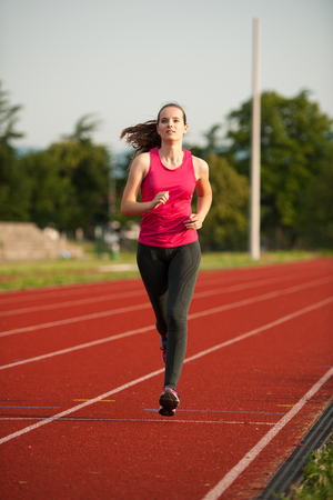 Beautiful young woman runner run on a track in early summer afternoon