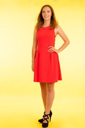 Beautiful young haapy woman in vibrant dre dress over yellow background .