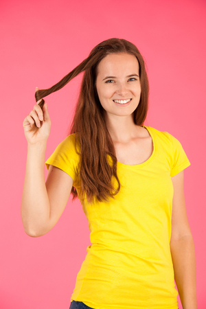 Woman in yellow t shirt holds her hair over vibrant pink background Stockfoto - 123117200