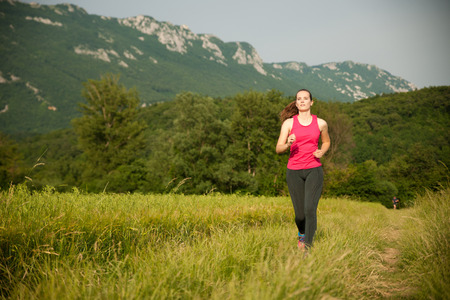 Beautiful young woman workout outdoor runs across meadow in early summer