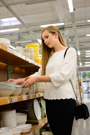 Beautiful young woman shopping dishes for her new home .