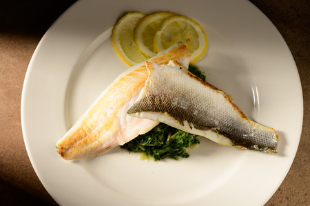 Roasted fish filet decorated with lemon slices on a plate