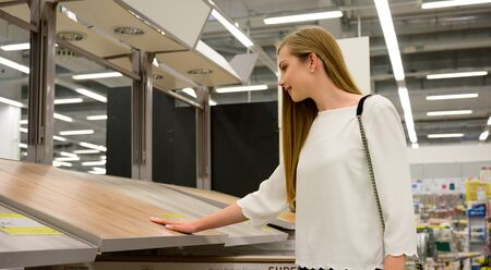Portrait of young smiling woman choosing wood laminated flooring in shop Stockfoto