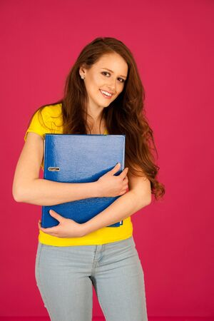 attractive young student in yellow t shirt holding red folder over pink background