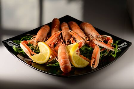 fresh grilled shrimps served on a plate with arugula or rocket and llemon Stockfoto