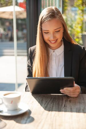 Beautiful business woman work on tablet in a bar and drink coffee 스톡 콘텐츠
