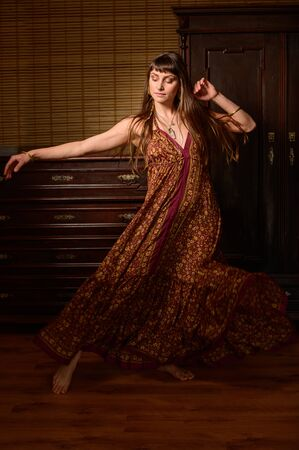Young girl dancer and singer in gypsy dress dancing and posing on stage .