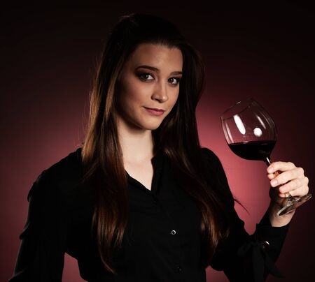 Beautiful young woman drink a glass of red wine over gradated red background