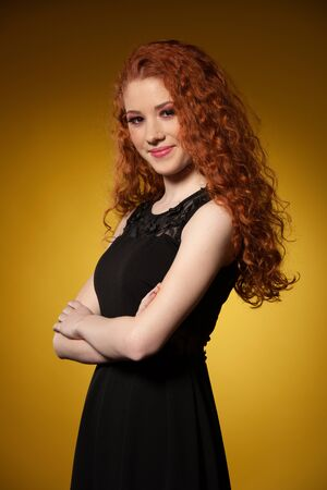 Beauty portrait of a preety redhead in black elegant dress over warm yellow background Banque d'images - 131326816