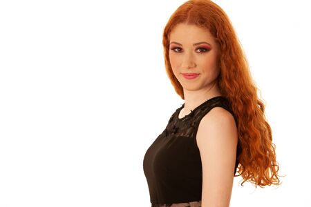 Beauty portrait of a preety redhead in black elegant dress over warm yellow background Banque d'images - 131326856