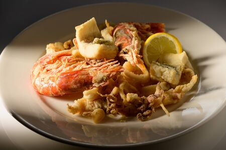Grilled Calamari (Squid) and shrimps with lemon and parsley on white plate on a plate in restaurant ready to be served