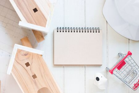Blank paper notebook with Miniature house model, blueprint plan, red cart and white safety helmet on white wood background, financial concept