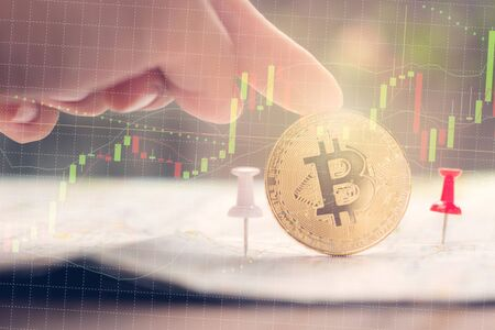 Finger touching golden bitcoin with Candlestick graph chart and red pin on map paper, Virtual digital currency and Financial investment trade concept