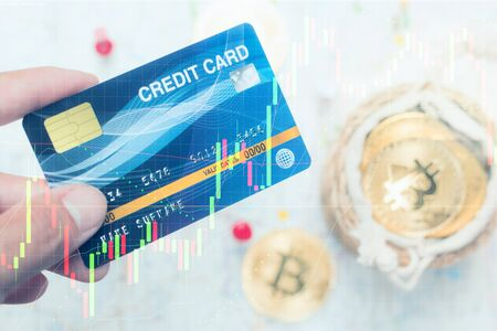 Close up hand holding credit card with Candlestick graph chart and blur background of stack bitcoin in basket, Virtual digital currency and Financial investment trade concept
