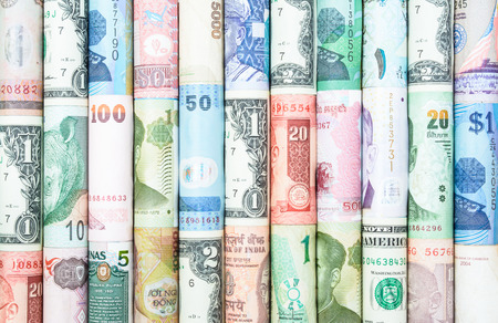 american currency: A backgrounds with colorful of many roll curreny from many country Stock Photo
