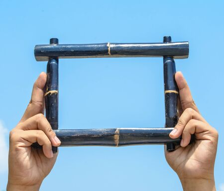 make my day: Two hands holding a black frame make it from bamboo with blue sky on sunshine day