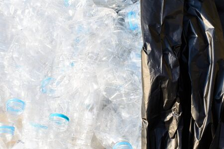 Background of plastic water bottles and black garbage bag ready for recycle Stock fotó