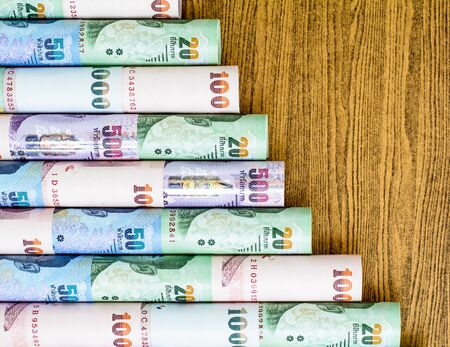 Colorful of Thai currency,banknotes roll put on wooden desk Stock fotó