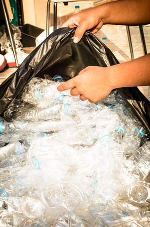 black plastic garbage bag: Save the world by our hands with separate plastic water bottles for recycle