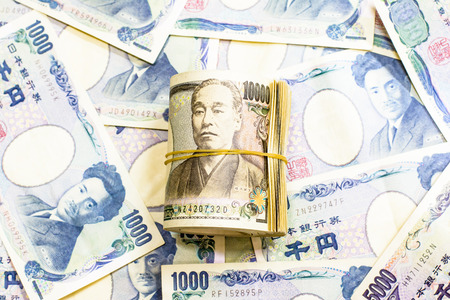 Background of  Japanese currency.Focus on roll of 10000 banknote on the middle