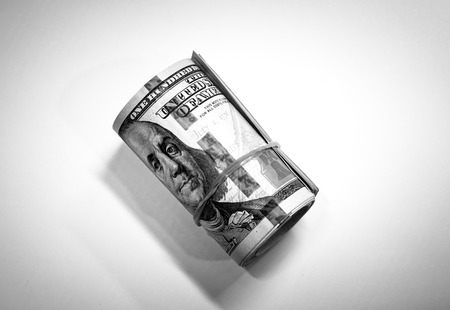 Roll background of hundred  dollars notes and shadow with black and white color