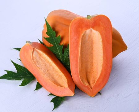 papaya seedless, cut in half with leaves on a white wooden floor