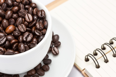 close up coffee bean in white cup and have blank notebook with ring binder at right hand side Stock Photo - 18663350
