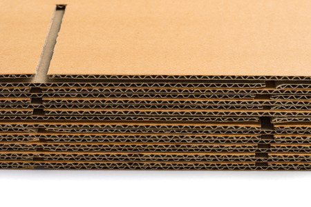 flattened: stack of corrugated cardboard boxes on white background. side perspective view of flattened boxes.
