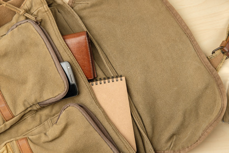 Men's bag stuff top view, navy-green fabric messenger bag have brown leather wallet, smartphone, notebook inside Imagens