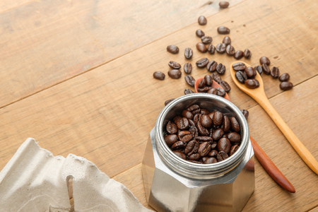 coffee beans on couple wood spoon and in a moka pot close to a take home tray of coffee cups on wooden table