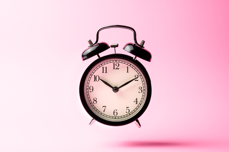 black vintage alarm clock floating on the air with pink color background
