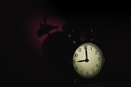 black vintage alarm clock in dark room with long shadow behind, low key tone picture Stock Photo