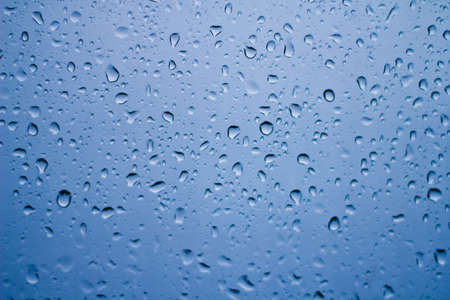 Close-up of water drops on glass surface as background._ Stock Photo