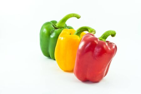 Red, yellow and green bell peppers isolated on the white background