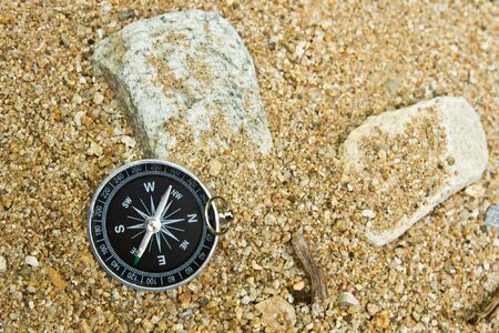 magnetic stones: compass on sand Stock Photo