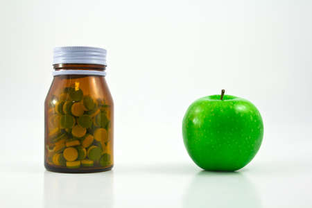 Medicine glass bottle with pills and apple
