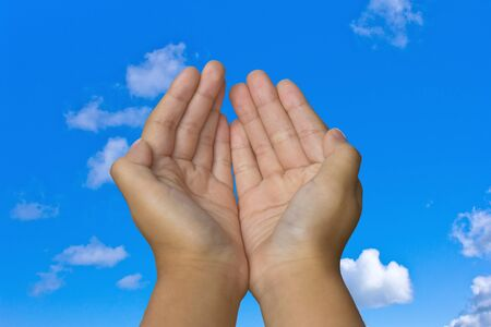 hand with blue sky and clouds Stock Photo