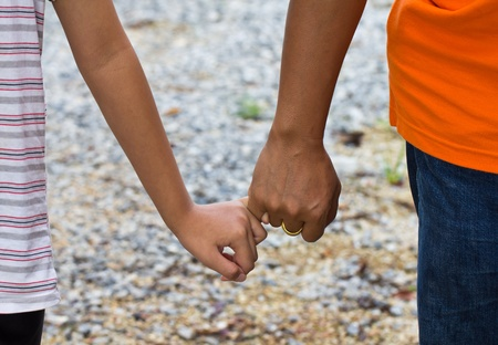 Pair of young people walking holding hands photo
