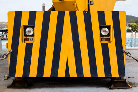 construction machine look like eye and face with yellow and black warning sign