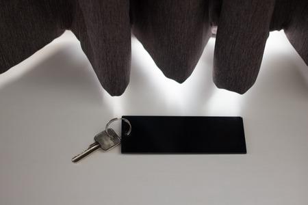 Blank hotel key in a shadow of curtain.