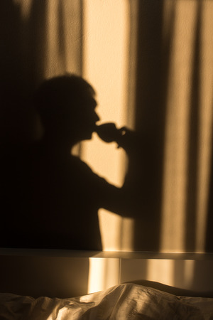 Shadow of man drinking coffee in the morning