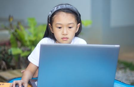 Cute little asian girl using laptop