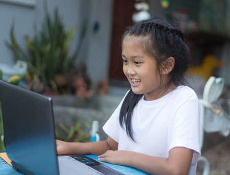 Cute little asian girl using laptop